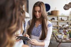 Paiement de autorisation de femme sur une tablette dans une boutique images libres de droits