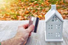 Paiement de concept d'utilités carte en plastique à disposition de l'homme et de modèle de mini maison Paiements pour la maison M Photos stock