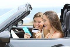 Paiement de touristes en ligne à l'intérieur d'une voiture de location des vacances images libres de droits