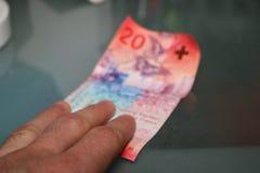 Paiement haut étroit d'homme avec les francs suisses Photographie stock libre de droits