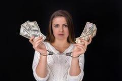 Paiement illicite du dollar divisé chez des mains de la femme dans des menottes image libre de droits