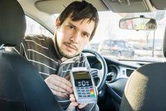 Paiement le transport Le chauffeur de taxi offre le terminal de paiement au client photographie stock libre de droits