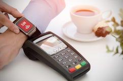 Paiement mobile en café avec la montre intelligente Photographie stock libre de droits