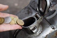Paiement pour le gaz, carburant, essence, concept diesel Argent de chute de main, pièce de monnaie dans la boîte de carburant image libre de droits