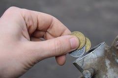 Paiement pour le gaz, carburant, essence, concept diesel Argent de chute de main, pièce de monnaie dans la boîte de carburant images stock