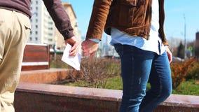 Paiements illicites de transfert dans la rue Un homme donne l'argent sous enveloppe à un autre homme marchant après l'un l'autre clips vidéos