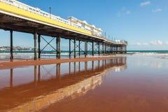Paignton Beach Devon England. Paignton pier reflected in the wet and on the Beach Devon England UK Europe stock photo