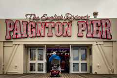 Paignton pier. Elderly disabled man on w wheelchair entering Paignton pier amusement arcade on a cloudy, stormy day Stock Photo
