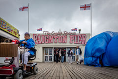 Paignton pier. Elderly disabled man on a wheelchair leaving Paignton pier amusement arcade on a cloudy, stormy day Stock Images