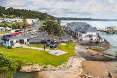 Paihia, North Island, New Zealand. Paihia, New Zealand - November 21, 2014: Sightseeing Helicopter landed in foreground, Ferry Terminal on right Royalty Free Stock Image