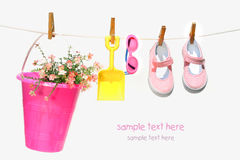 Pail,sunglasses and shoes for child. On clothesline Royalty Free Stock Photography