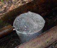 Pailful di acqua che riempie dal tubo Fotografia Stock Libera da Diritti