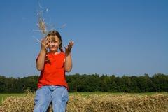 Paille de projection de fille de ferme dans l'air. Image stock