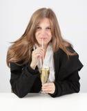 Paille sirotante du champagne W de fille Photo stock