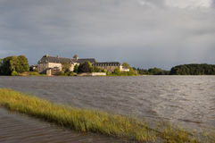Paimpont abbey viewed from the lake. With a cloudy sky Royalty Free Stock Photos