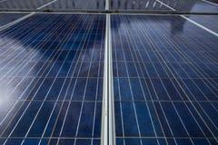 Painéis azuis da célula solar que mostrados suas linha e texturas de superfície de grade Os painéis estão contra a luz do sol no  imagem de stock