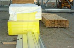 Painéis empilhados de madeira da madeira compensada ou do gyproc cobertos com um encerado no canteiro de obras Imagem de Stock