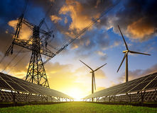 Painéis solares com turbinas eólicas e pilão da eletricidade no por do sol fotografia de stock
