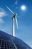 Painéis solares e turbina de vento de encontro a um céu ensolarado Foto de Stock