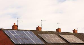 Painéis solares em partes superiores, em céu e em nuvens do telhado Fotografia de Stock