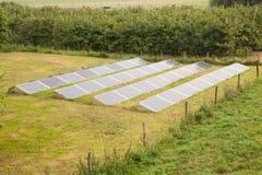 Painéis solares na grama de um jardim Imagem de Stock Royalty Free