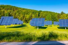 Painéis solares no campo ao longo da estrada Fotografia de Stock