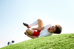 Pain. Image of soccer player lying down and shouting in pain Royalty Free Stock Image