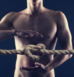 Pain in the abdomen or in the stomach of man. Heartburn. Male torso on a background image of a rope knot Royalty Free Stock Image