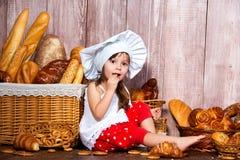 Pain autour de la tête Peu fille de sourire dans un chapeau de cuisinier mange le pain et des bagels près d'un panier en osier av photos libres de droits