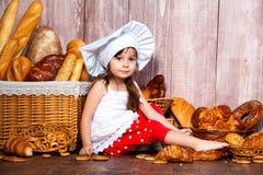 Pain autour de la tête Peu fille de sourire dans un chapeau de cuisinier mange le pain et des bagels près d'un panier en osier av photos stock