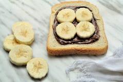 Pain avec de la crème de chocolat et la banane coupée en tranches Images libres de droits