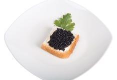 Pain avec du beurre et le caviar d'isolement sur un fond blanc Images stock