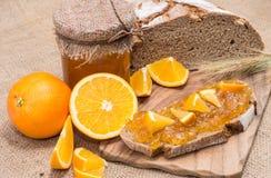 Pain avec la confiture d'oranges (fond rustique) Photo stock