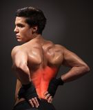 Pain in back. Man with pain his back highlighted with red holding waist Royalty Free Stock Photography