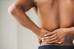 Pain in back. Cropped image of young African man touching his back Stock Photography