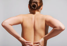 Pain in back spine. Nude woman touching her back. Medical problem with spine Royalty Free Stock Images
