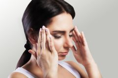 Pain. A beautiful woman on a gray background, stress and headache with migraine headaches, she wrestled with pain, a big portrait, Royalty Free Stock Image