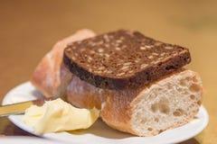 Pain blanc et noir avec du beurre Photographie stock