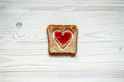 Pain blanc grillé avec un coeur à l'intérieur Au coeur plâtré avec de la confiture de framboise Le pain grillé est sur une surfac Photo libre de droits