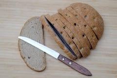 Pain brun coupé en tranches sur le bureau en bois image libre de droits