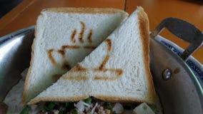 Pain chaud avec du café chaud dessiné sur l'oeuf au plat avec la côtelette de porc dans la petite casserole pour le petit déjeune Photographie stock