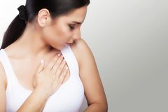 Pain. Close-up of a young woman feels severe chest pain. Close-up of a woman`s body with a hand on her chest. The girl suffers fr. Om a painful feeling that has Royalty Free Stock Photos