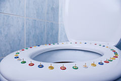Pain. Colorful pins on a toilet seat Stock Photography