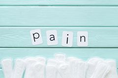 Pain copy for menstrual period concept with sanitary pads on mint green wooden background top view copy space. Woman hygiene. Pain copy for menstrual period stock photos