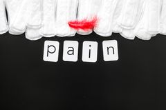 Pain copy for menstrual period concept with sanitary pads and red feather on black background top view mock-up royalty free stock photography