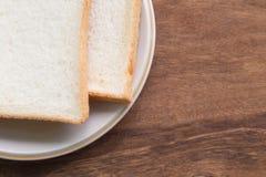 Pain coupé en tranches dans le plat sur le fond en bois photo stock
