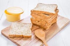 Pain coupé en tranches de blé entier avec du beurre sur la table en bois blanche Photographie stock