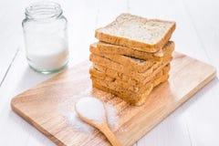 Pain coupé en tranches de blé entier avec du sucre sur la table en bois blanche Photo stock