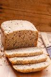 Pain coupé en tranches de blé entier sur la planche à découper Photo libre de droits