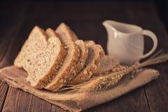 pain coupé en tranches de blé entier sur la table en bois, backgroun d'obscurité de vintage Photos libres de droits